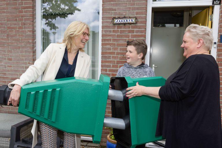 Met een symbolische groene stekker feliciteert manager Volkshuisvesting Wieke van Veldhuizen van Portaal de familie Jager uit Nijmegen met hun zojuist geplaatste zonnepanelen.